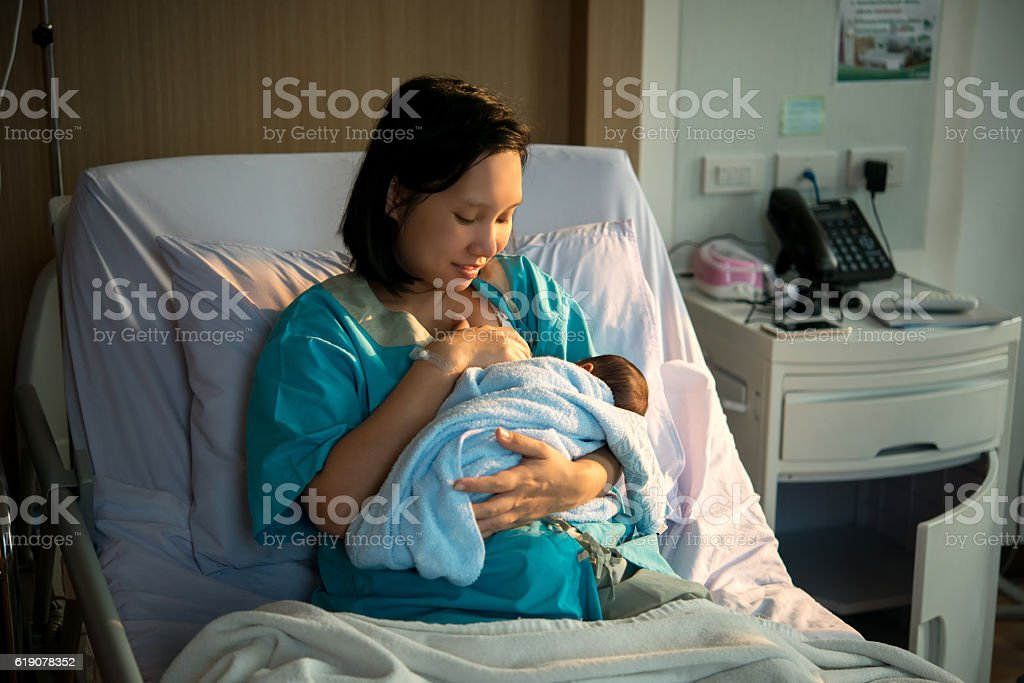 Mothers breastfeed while dating a beautiful golden sunset. - foto de stock