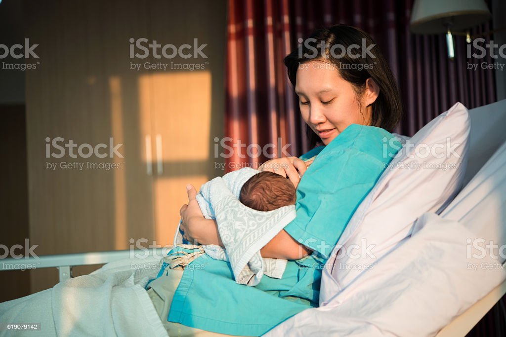 Mothers breastfeed while dating a beautiful golden sunset. stock photo