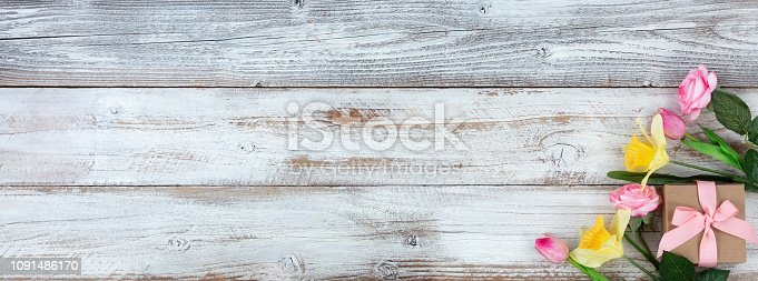 921112244 istock photo Mothers Day and Easter holiday concept on white rustic background with a decorated gift box and variety of flowers 1091486170