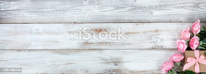 istock Mothers Day and Easter holiday concept on white rustic background with a decorated gift box and pink roses 1091486194