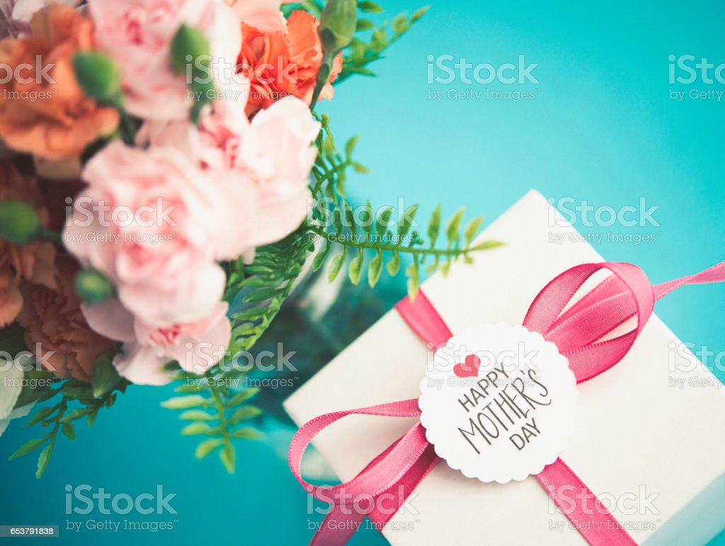 Mother's Day arrangement with gift and fresh carnations stock photo