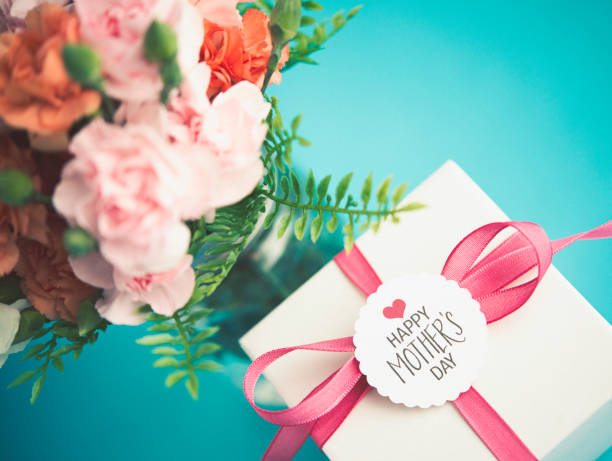 mother's day arrangement with gift and fresh carnations - gift tag note stock photos and pictures