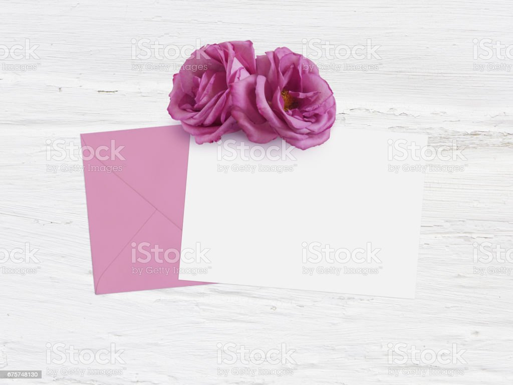 Mothers day, birthday or wedding mockup scene with envelope, blank card and rose flowers. Grunge white background, flat lay image, top view stock photo