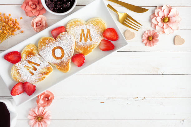 Mothers Day breakfast heart shaped pancakes with MOM letters, top view corner border on a white wood background stock photo