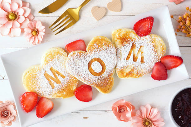 Mothers Day breakfast heart shaped pancakes with MOM letters, top view table scene on white wood stock photo