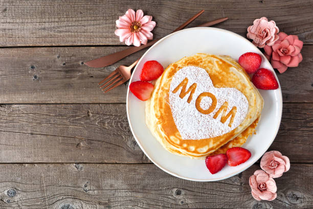 Mothers Day breakfast pancakes with heart shape and MOM letters, top view on rustic wood stock photo