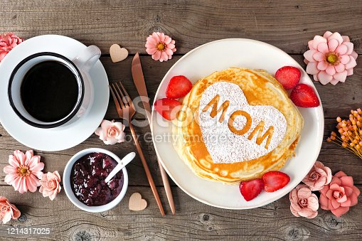 Pancakes with heart shape and MOM letters. Mothers Day breakfast concept. Overhead view table scene with a rustic wood background.