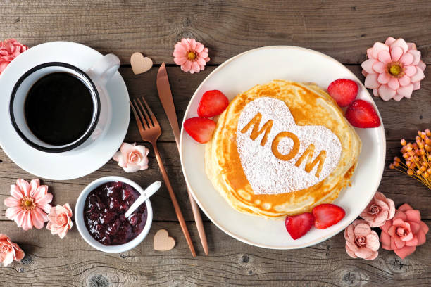 Mothers Day breakfast pancakes with heart shape and MOM letters, overhead view table scene on rustic wood stock photo