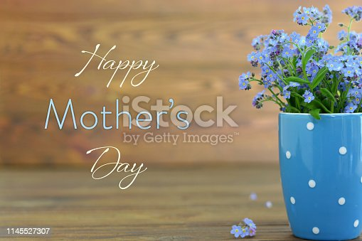 Mothers Day card with flowers in the cup on wooden background