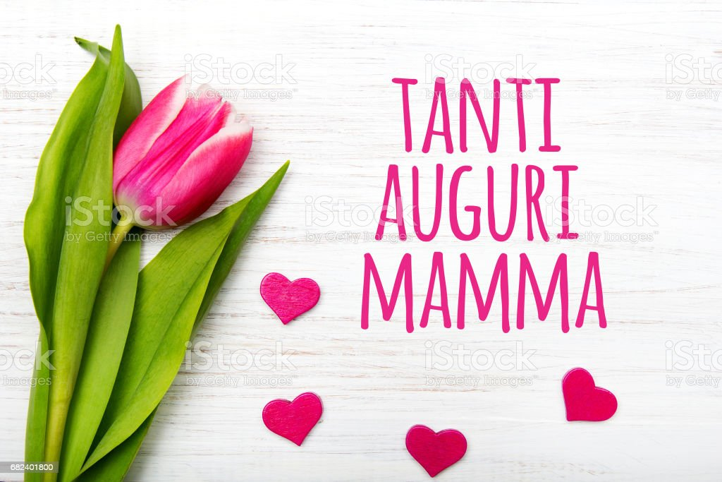 Mother's day card with Italian words: Happy mother's day. Tulip flower and small hearts on white wooden background, copy space royalty-free stock photo