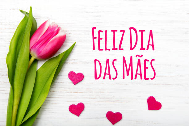 Mother's day card with  Portuguese words: Happy Mother's day, and pink tulip on white wooden background. stock photo