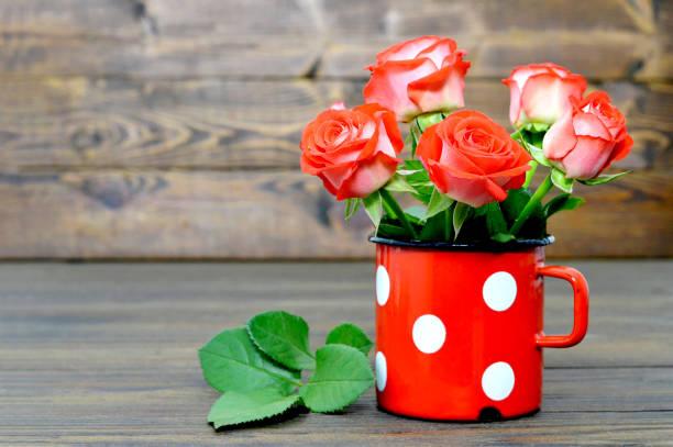 Carte fête des mères avec des roses rouges dans l'ancienne coupe - Photo