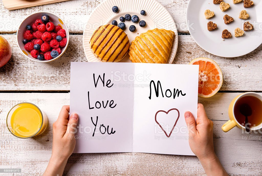 Mothers day composition. Greeting card and breakfast meal. Mothers day composition. Hands of unrecognizable woman holding greeting card with We love you, Mom, text. Breakfast meal. Studio shot on wooden background. Adult Stock Photo