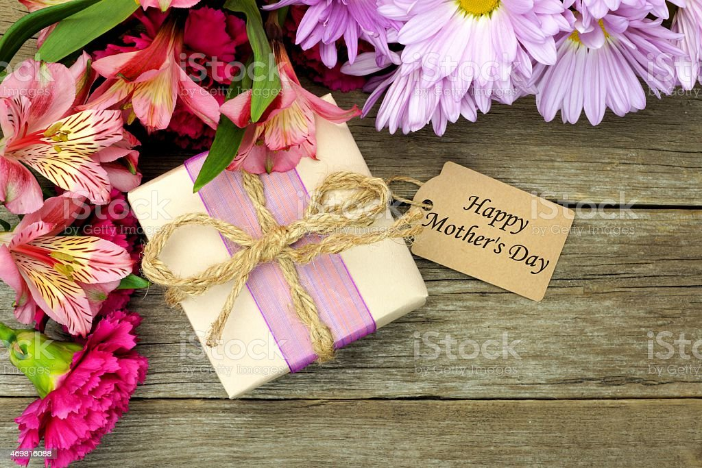 Border of flowers with gift box and Happy Mother\'s Day tag against a...