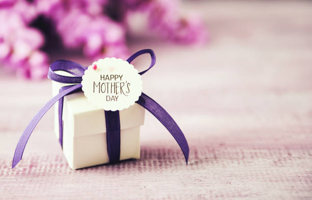 Mother's Day gift box with purple ribbon and wisteria bouquet Mother's Day gift box with purple ribbon and wisteria bouquet mothers day stock pictures, royalty-free photos & images