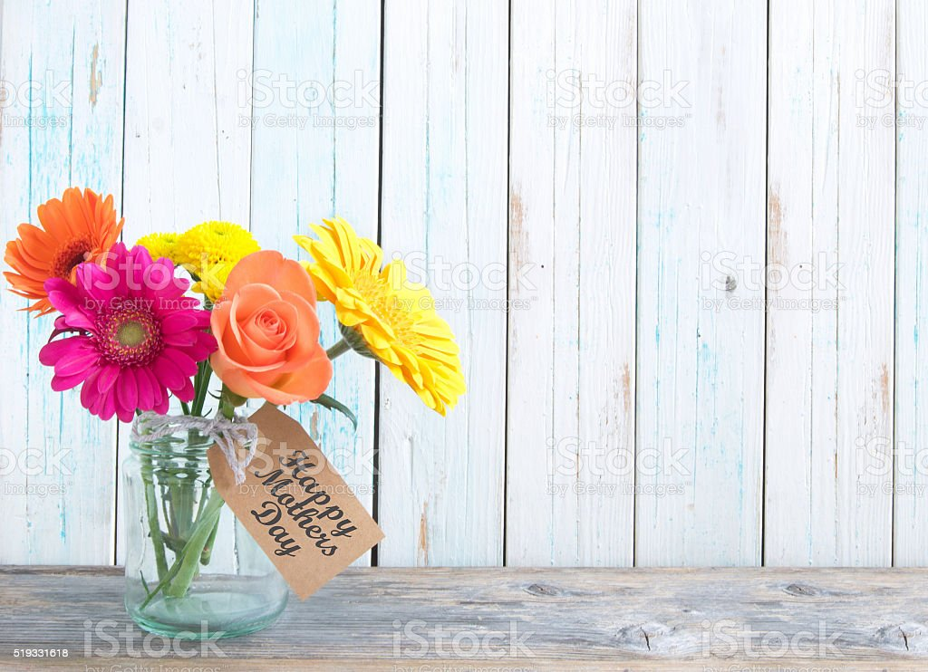 Mixed variety of flowers in a glass jar over a white background with...