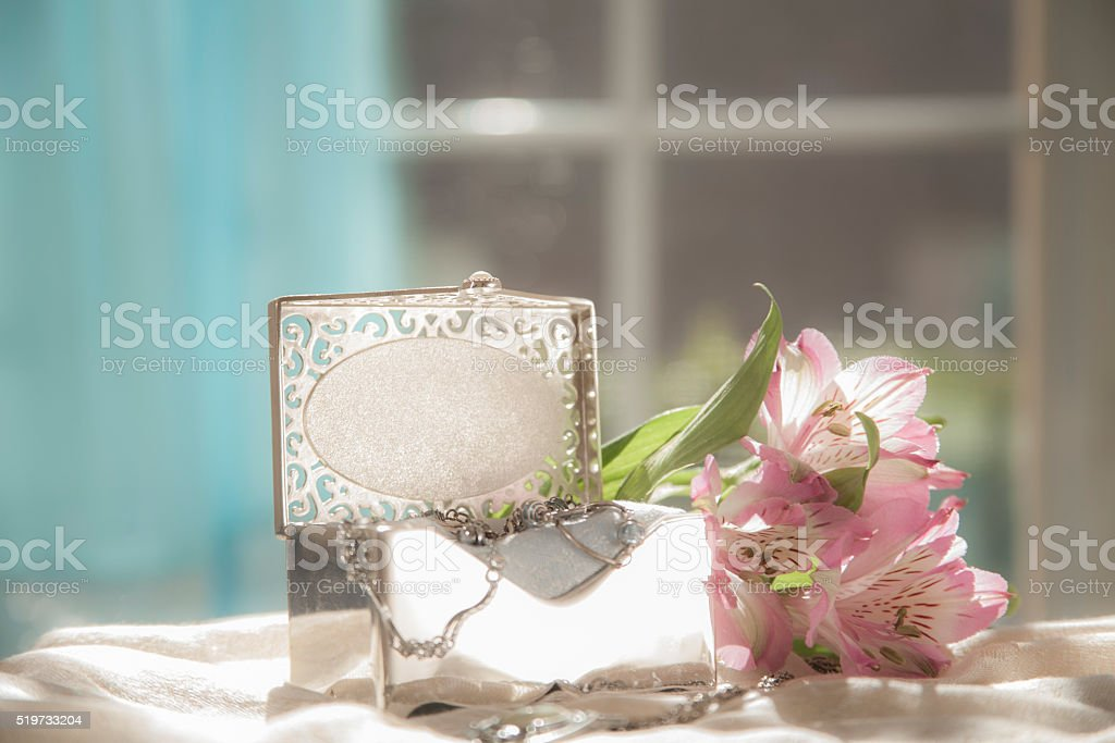 Mother\'s Day memories. Feminine, silver jewelry box lies open on top...