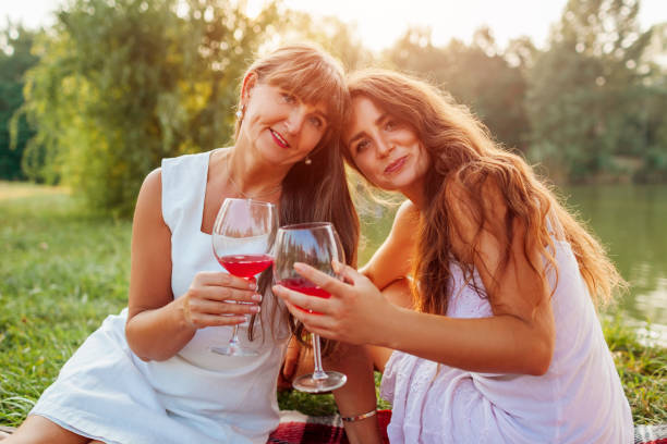 Mother's day. Mother drinking wine with her adult daughter in spring park. Family having picnic outdoors. stock photo