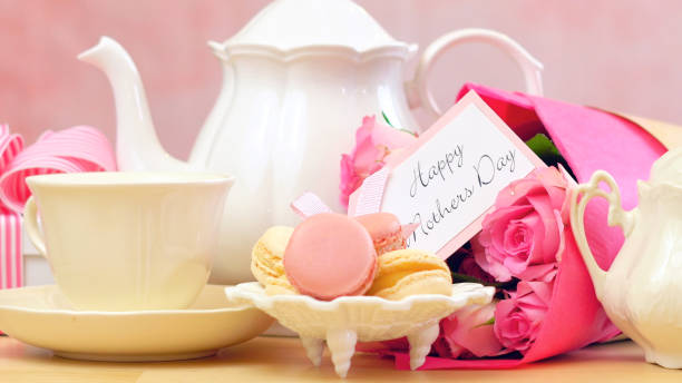 Mother's Day tea setting with macaron cookies, pink roses and gift, closeup stock photo