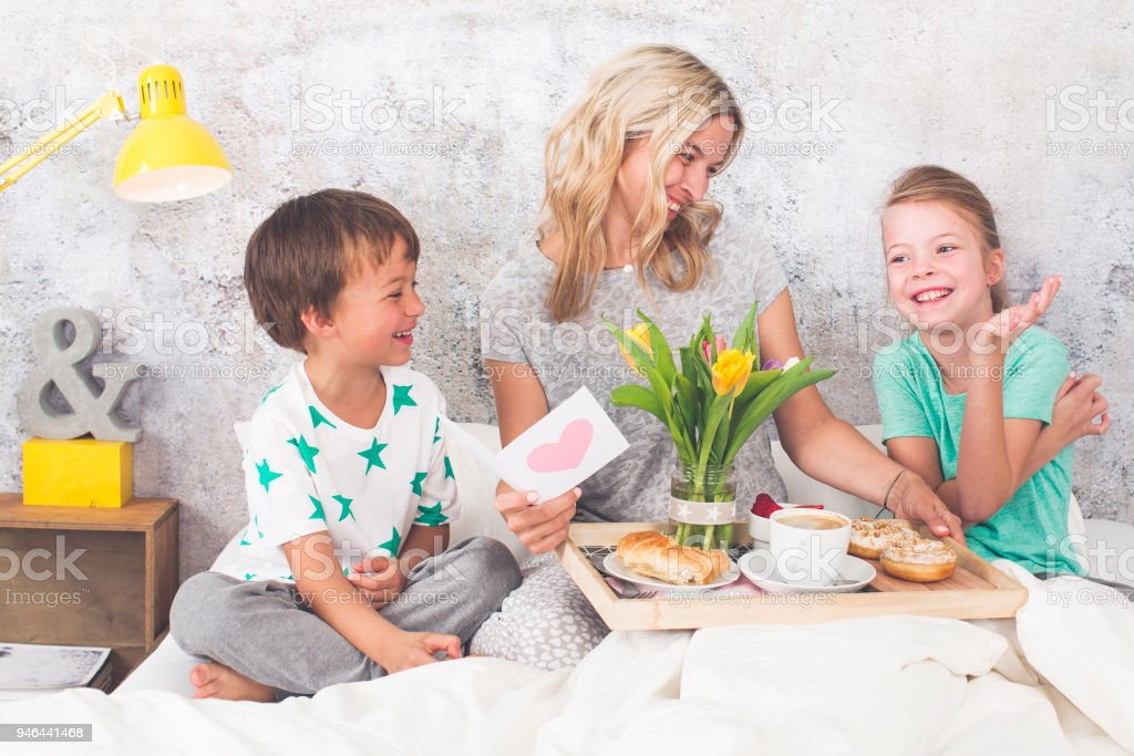 Mother´s Day - two children surprise their mother with breakfast in modern bed stock photo