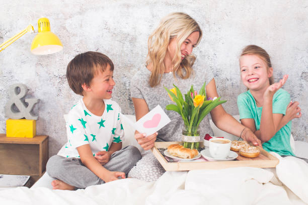 mother′s day - two children surprise their mother with breakfast in modern bed - mothers day stock pictures, royalty-free photos & images