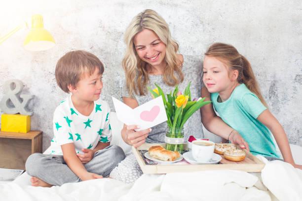 Mutter Tag - zwei Kinder überraschen Sie ihre Mutter mit einem Frühstück im modernen Bett – Foto