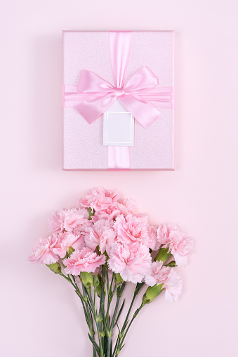 Mother's Day, Valentine's Day background design concept, beautiful pink carnation flower bouquet on pastel pink table, top view, flat lay, copy space.