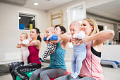 Group of fit young mothers and their babies in modern gym doing exercises on gymnastic balls. Healthy lifestyle.