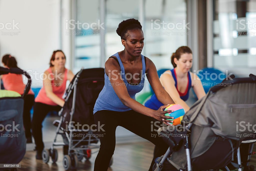 Mothers Exercising with Their Babies in a Gym stock photo