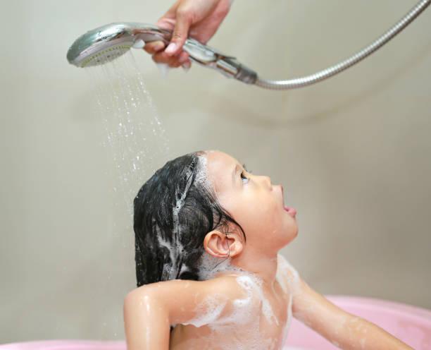mutters hand gießt wasser aus dusche, kleinen mädchen die haare zu waschen. - mädchen dusche stock-fotos und bilder