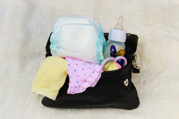 mutters handtasche mit artikeln zur betreuung des kindes auf weißem hintergrund. ansicht von oben. - kinderhandtaschen stock-fotos und bilder