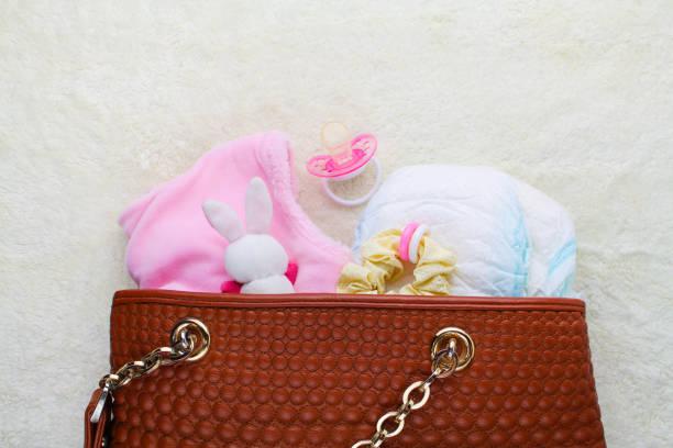 mother's handbag with items to care for child - kinderhandtaschen stock-fotos und bilder