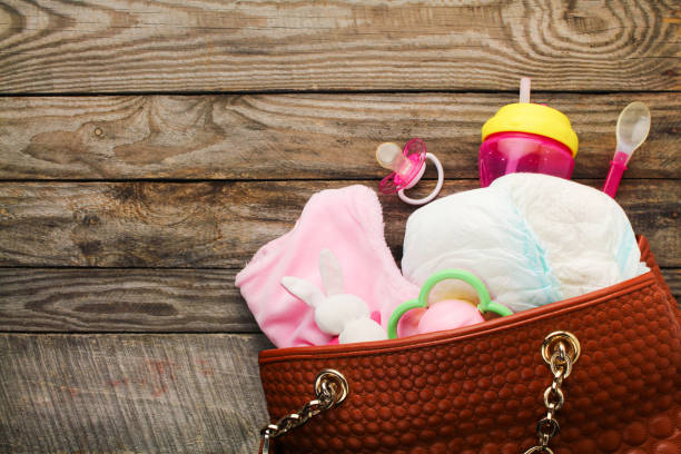 mother's handbag with items to care for child - group of objects stock pictures, royalty-free photos & images