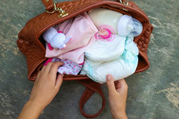 mutters handtasche mit artikeln um für kinderbetreuung. die hände von frauen nehmen dinge aus der tasche. - babytasche stock-fotos und bilder
