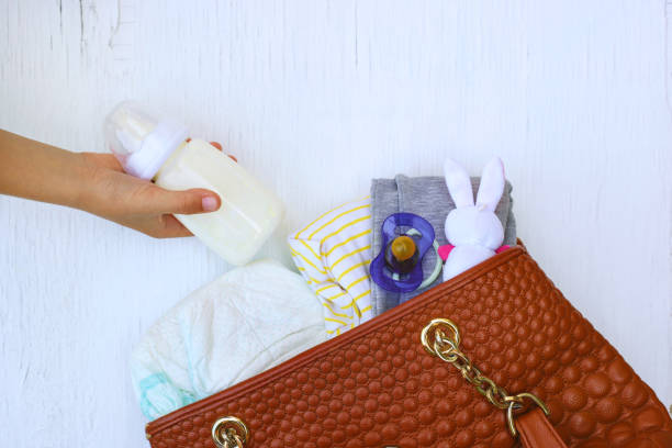 mutters handtasche mit artikeln um für kinderbetreuung. die hände von frauen nehmen dinge aus der tasche. - kinderhandtaschen stock-fotos und bilder