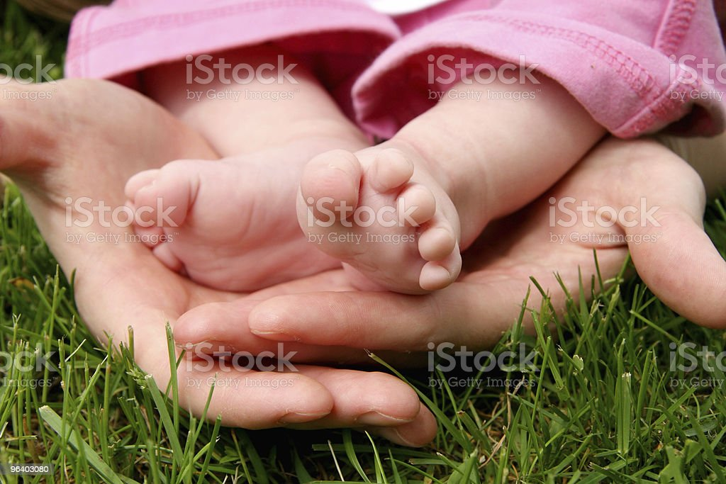 Mother's hands cradling her infant Daughter's feet - Royalty-free Adult Stock Photo