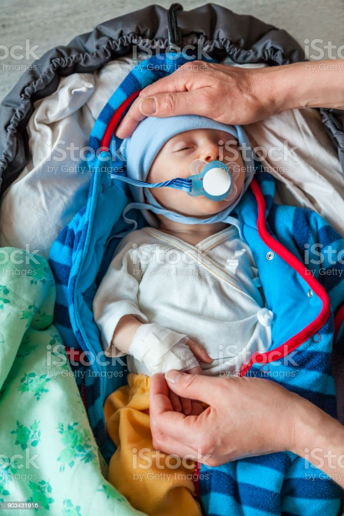 Mothers hands holding a sick infant boy patient with a pacifier and bandage on his hand, seen from above. royalty-free stock photo