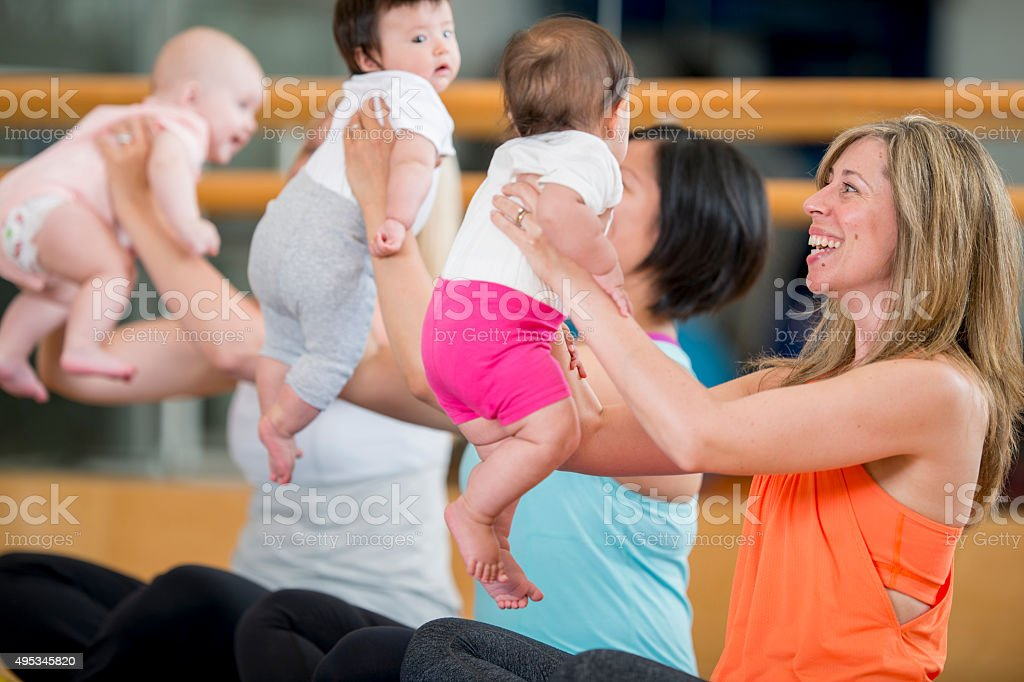 Mothers Holding Their Babies in a Yoga Class stock photo