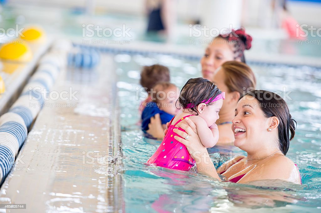 Mothers teaching their babies to swim stock photo