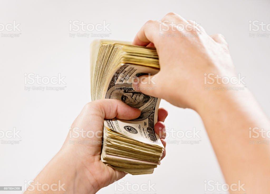 Motion blur as female hand counts hundred dollar bills stock photo