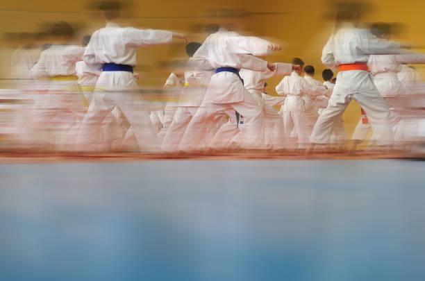 desenfoque de movimiento borrosa de fondo. formación de los niños en karate. - artes marciales fotografías e imágenes de stock