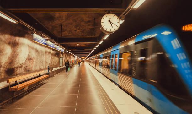 hareket bulanıklığı metro tren metro istasyonu ile saat sürüş üzerinden - sefer tarifesi stok fotoğraflar ve resimler