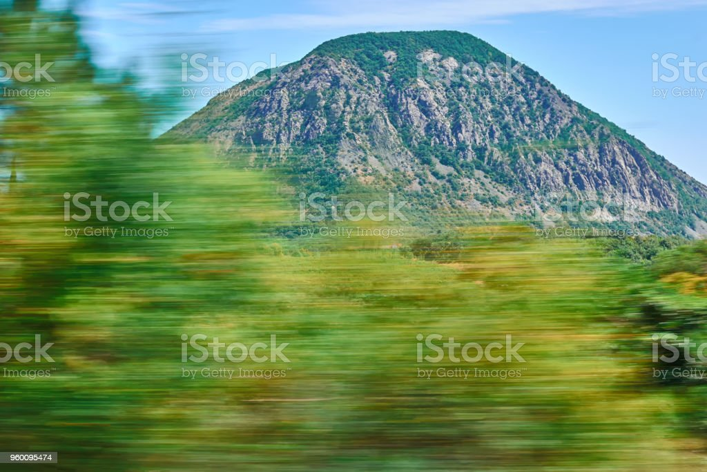 Motion blur image folliage when driving fast on the road. Against the mountains on a clear Sunny day. stock photo