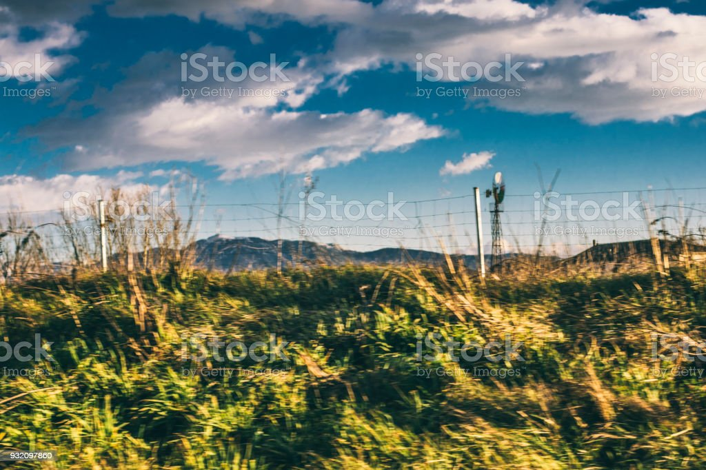 Motion blur landscape with green herbs and blue sky cloudscape stock photo
