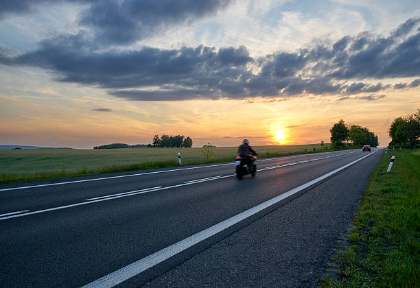Motion blur motorcycle riding on the asphalt road at sunset. – Foto