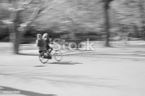 Motion blur of a cyclist and pillion passenger in Vondelpark, Amsterdam, Netherlands