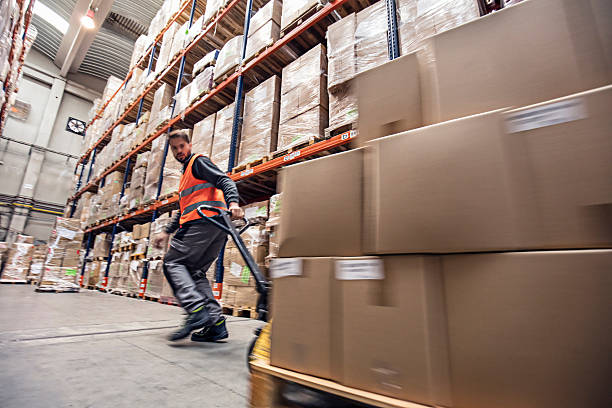 Motion blur of a man moving boxes in a warehouse Motion blur of a man moving boxes in a warehouse. pallet jack stock pictures, royalty-free photos & images