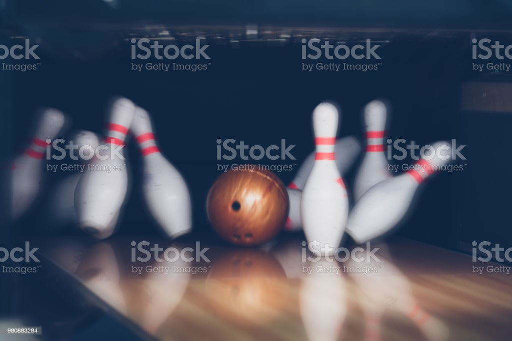 motion blur of bowling ball and skittles on the playing field stock photo