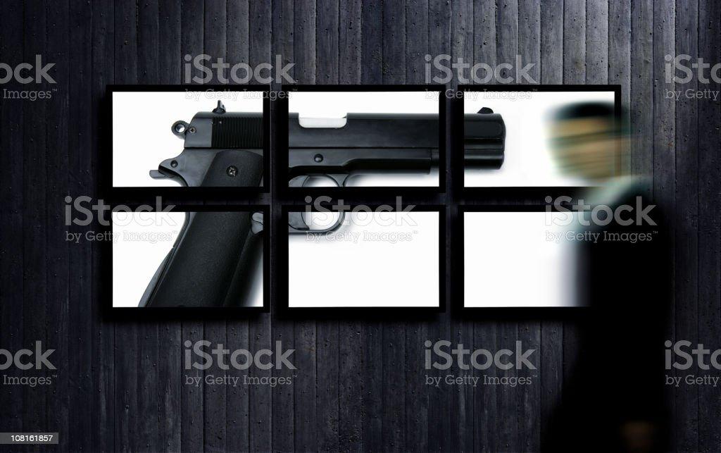 Motion Blur of Businessman Walking By Flat Screens Displaying Handgun royalty-free stock photo