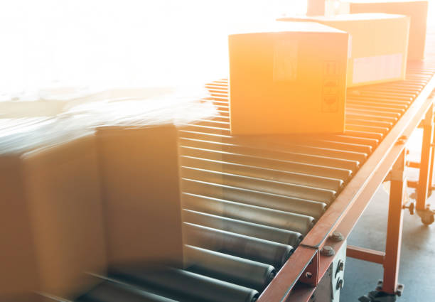 Motion blur of cardboard parcel boxes on rollers conveyor Motion blur of cardboard parcel boxes on rollers conveyor distribution center stock pictures, royalty-free photos & images